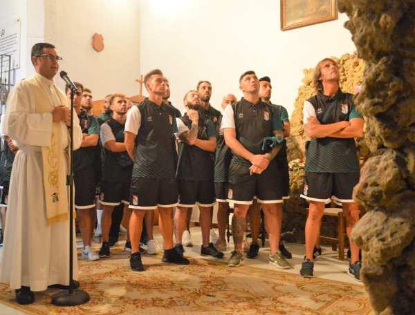 Los jugadores del Puerto Real CF observan a la Virgen de Lourdes de Puerto Real.